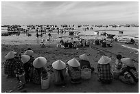 Women with conical hats sit on beach as fresh catch arrives. Mui Ne, Vietnam ( black and white)