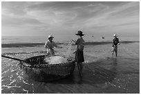 Fishermen folding fishing net into coracle boat. Mui Ne, Vietnam ( black and white)