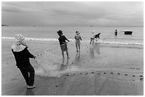 Fishermen lining up to pull net onto beach. Mui Ne, Vietnam ( black and white)