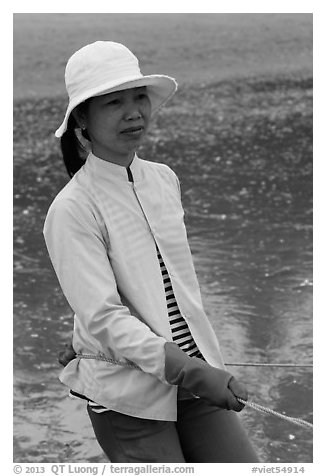 Fisherwoman pulling net line. Mui Ne, Vietnam (black and white)