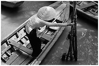 Woman in ao dai reaching to bamboo poles from boat. My Tho, Vietnam (black and white)