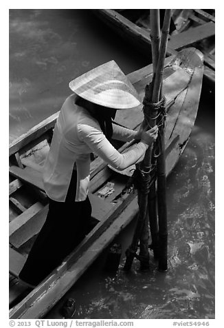 Woman in Ao Ba Ba holding from boat to bamboo poles. My Tho, Vietnam (black and white)