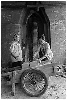 Workers loading bricks out of brick oven. Mekong Delta, Vietnam ( black and white)