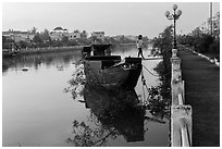 Woman in high heels walking out of barge. Tra Vinh, Vietnam ( black and white)