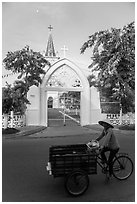 Woman bicycling in front of church. Tra Vinh, Vietnam ( black and white)