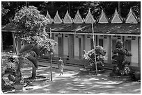 Monk walking past huts, Hang Pagoda. Tra Vinh, Vietnam ( black and white)