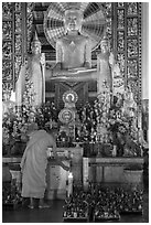 Monk lighting incense at  Ang Pagoda altar. Tra Vinh, Vietnam ( black and white)