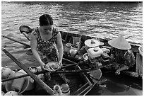 Woman gets bowl of noodles from floating market. Can Tho, Vietnam ( black and white)