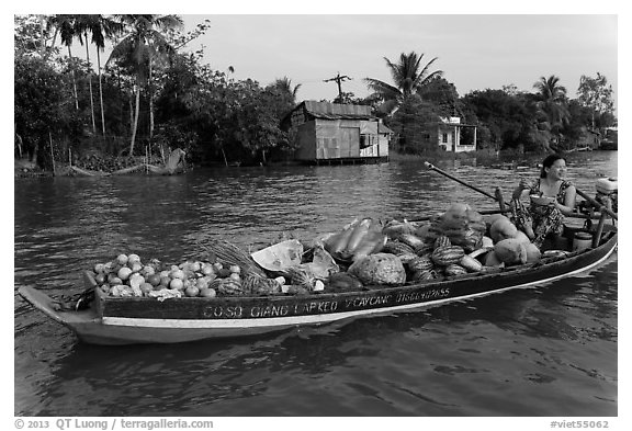 Woman with boat loaded with produce eating noodles. Can Tho, Vietnam (black and white)