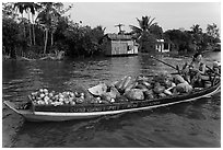 Woman with boat loaded with produce eating noodles. Can Tho, Vietnam ( black and white)