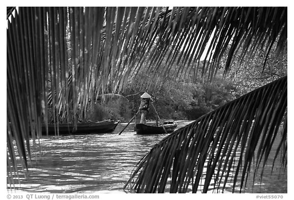 Woman paddling boat on river channel, framed by leaves. Can Tho, Vietnam (black and white)