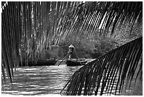 Woman paddling boat on river channel, framed by leaves. Can Tho, Vietnam ( black and white)