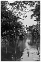 Woman walking across monkey bridge. Can Tho, Vietnam ( black and white)