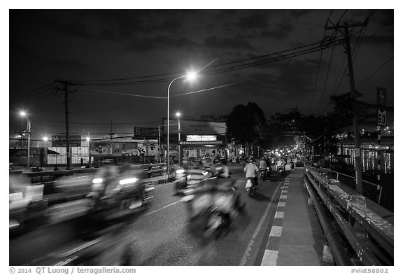 Evening traffic by the canal, District 8. Ho Chi Minh City, Vietnam (black and white)