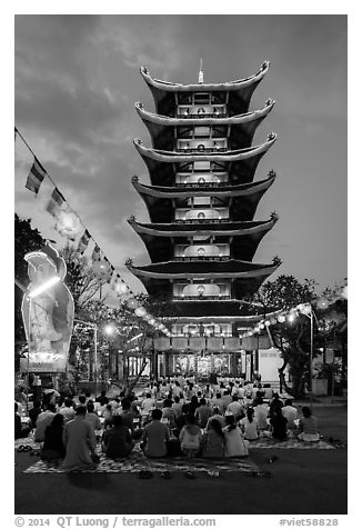Worshippers and seven story  Quoc Tu pagoda at dusk. Ho Chi Minh City, Vietnam (black and white)