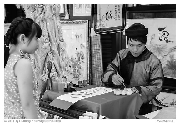 Caligrapher draws Tet greetings as woman looks on. Ho Chi Minh City, Vietnam (black and white)