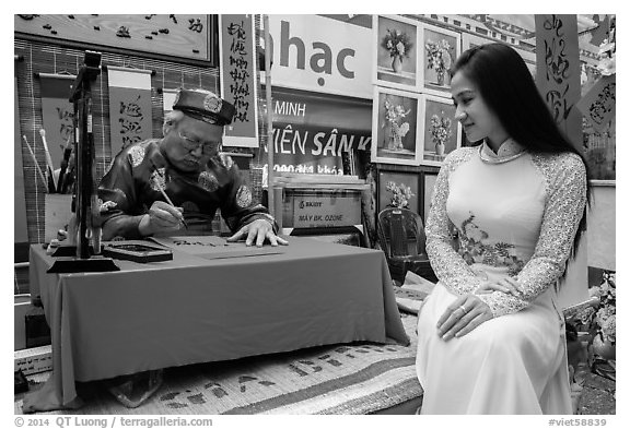 Caligrapher draws lunar new year greetings for beautiful woman in ao ai. Ho Chi Minh City, Vietnam (black and white)