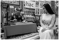 Caligrapher draws lunar new year greetings for beautiful woman in ao ai. Ho Chi Minh City, Vietnam ( black and white)