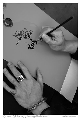 Hands drawing Tet greetings in ornamented characters. Ho Chi Minh City, Vietnam (black and white)