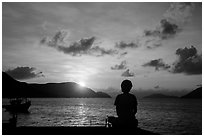 Sitting woman in silhouette and sunrise, Con Son. Con Dao Islands, Vietnam ( black and white)