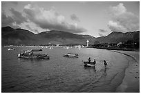 Woman collects catch from fishermen on coracle boat, Con Son. Con Dao Islands, Vietnam ( black and white)