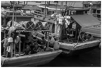 Sailors and families take lunch break at the back of boats, Ben Dam. Con Dao Islands, Vietnam ( black and white)