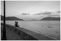 Young women sitting on seawall, evening, Con Son. Con Dao Islands, Vietnam ( black and white)