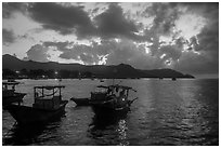 Men with light on fishing boat at dawn, Con Son harbor. Con Dao Islands, Vietnam ( black and white)