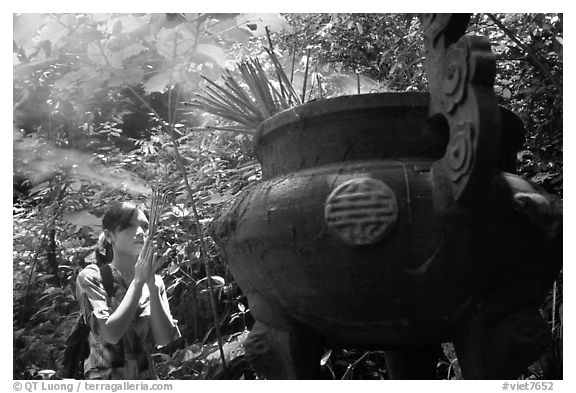Tourist praying at an urn with incense near the entrance of Phong Nha Cave. Vietnam (black and white)