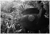 Visitor praying at an urn with incense near the entrance of Phong Nha Cave. Vietnam (black and white)