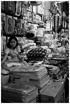 Vendor sitting amongst Abondance of cheap goods imported from nearby China at the Dong Kinh Market. Lang Son, Northest Vietnam (black and white)