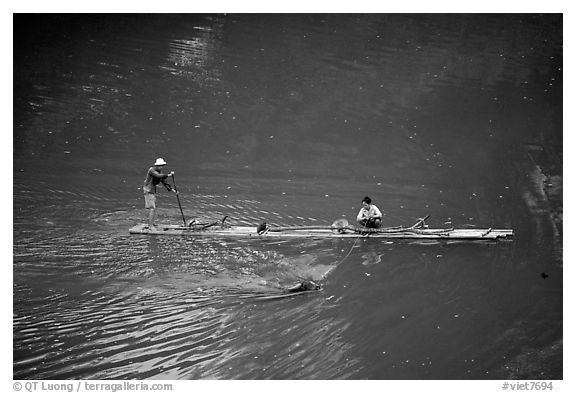 Crossing the Ky Cung  River on a narrow dugout boat. Northest Vietnam (black and white)