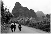 Villagers in traditional garb walking down the road with limestone peaks in the background, Ma Phuoc Pass area. Northeast Vietnam ( black and white)
