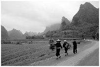 Villagers walking down the road with limestone peaks in the background, Ma Phuoc Pass area. Northeast Vietnam (black and white)