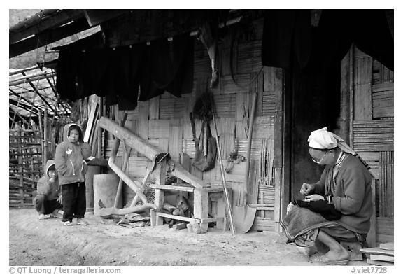 Elderly woman sewing  on her doorstep as kids look up. Northeast Vietnam (black and white)