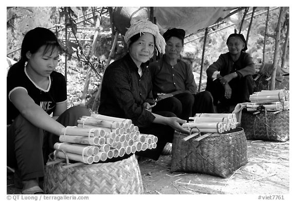 Women selling sweet rice cooked in bamboo tubes. Vietnam (black and white)