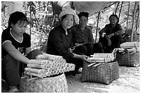Women selling sweet rice cooked in bamboo tubes. Vietnam ( black and white)