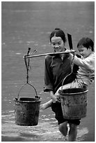 Woman of the Tay minority carrying crossing the river with child, Ba Be Lake. Vietnam (black and white)