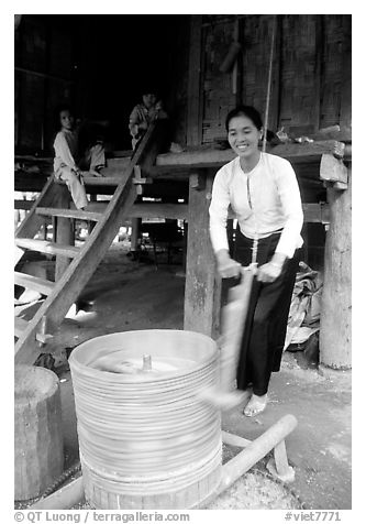 Woman of the Thai ethnicity milling grain, near Mai Chau. Northwest Vietnam (black and white)
