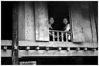 Two thai women at the window of their stilt house, Ban Lac village. Northwest Vietnam (black and white)