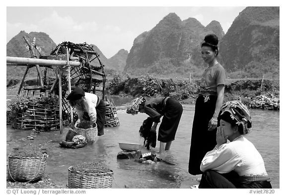 Thai women washing laundry and collecting water plants near an irrigation wheel, near Son La. Northwest Vietnam (black and white)