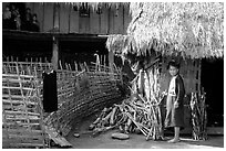 Woman in front of her hut and family on stilt house, between Lai Chau and Tam Duong. Northwest Vietnam (black and white)