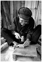 Dzao man crafting the decorative coins used in the children hats, between Tam Duong and Sapa. Northwest Vietnam (black and white)