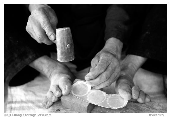 Hands and feet of a Black Dzao man making decorative coins, between Tam Duong and Sapa. Northwest Vietnam