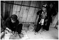 Black Dzao children look at a man  making the decorative coins used on their hats, between Tam Duong and Sapa. Northwest Vietnam (black and white)