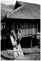 Montagnard child carries logs out of her house, between Tuan Giao and Lai Chau. Northwest Vietnam ( black and white)