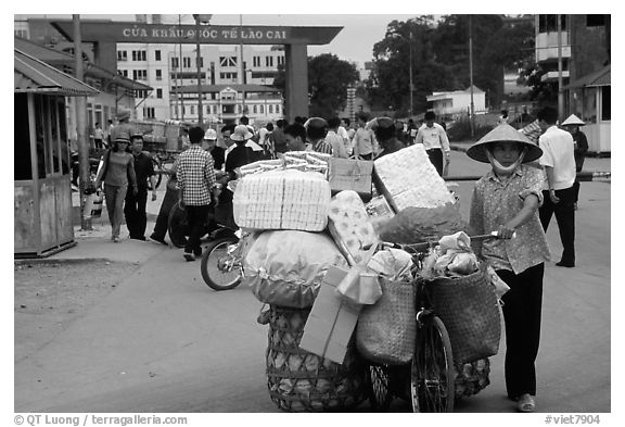 Woman pushing a bicycle loaded with cheap goods at the Lao Cai border crossing. Vietnam