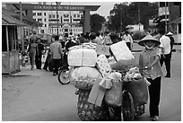 Woman pushing a bicycle loaded with cheap goods at the Lao Cai border crossing. Vietnam (black and white)