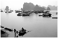 Rowboat meeting woman on shore. Halong Bay, Vietnam (black and white)