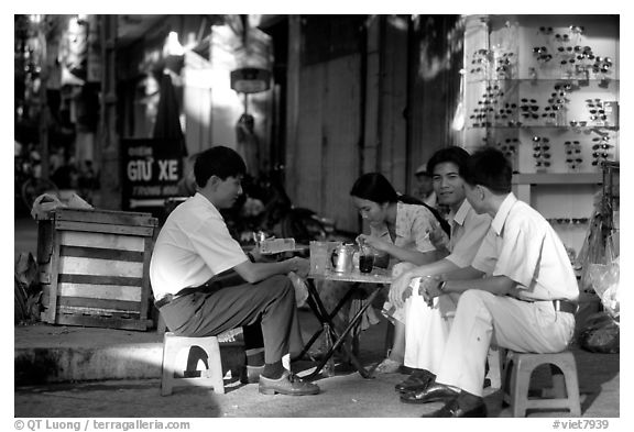 Enjoying a cafe on the streets, sitting on the typical tiny chairs. Ho Chi Minh City, Vietnam (black and white)